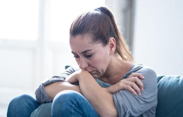 Young attractive latin woman lying at home living room couch feeling sad | Common symptoms of depleted B12 stores include: | Vitamin B12 Deficiency Symptoms and FAQ for Vegans
