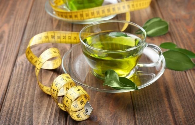 a cup of green and a yellow tape measure | Weight Loss | 8 Benefits of A Green Tea Shot for Your Health