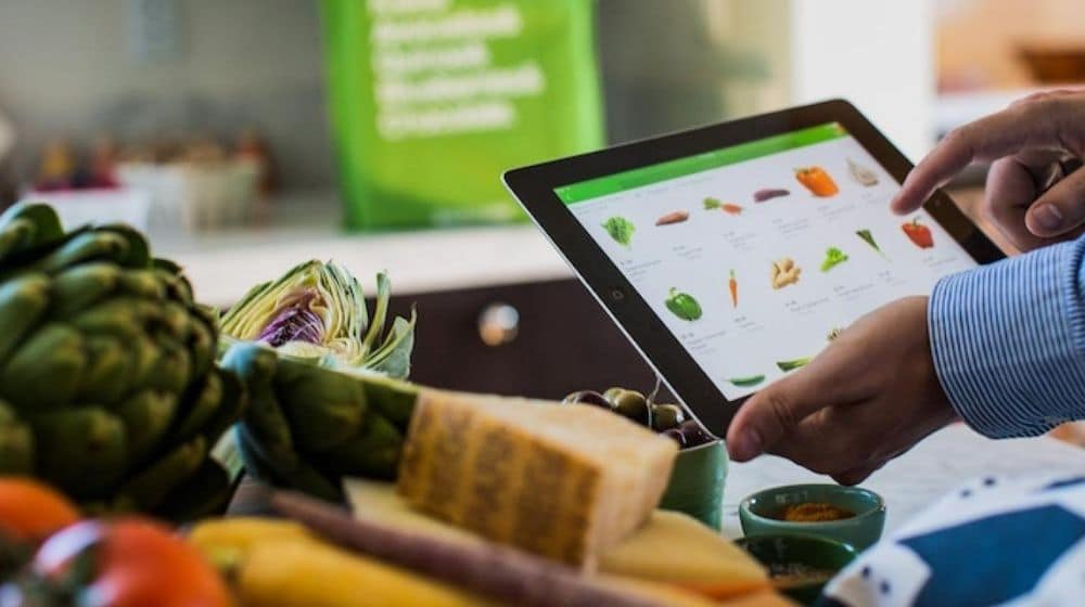 a hand holding a tablet which shows some kind of vegan food | Ask for Their Vegan Menu | Vegan Fast Food: Your Guide To Ordering Out