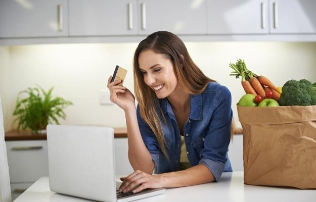 a woman smiling and holding credit card after ordering vegan food | Make An Online Review or Write on Their Comment Card | Vegan Fast Food: Your Guide for Ordering Out