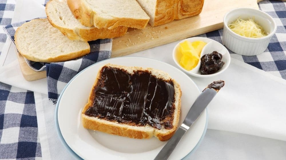sandwiches with marmite with a knife aside next to a small dish of cheesese | Feature | Have You Heard of Marmite? Find Out About This British Staple