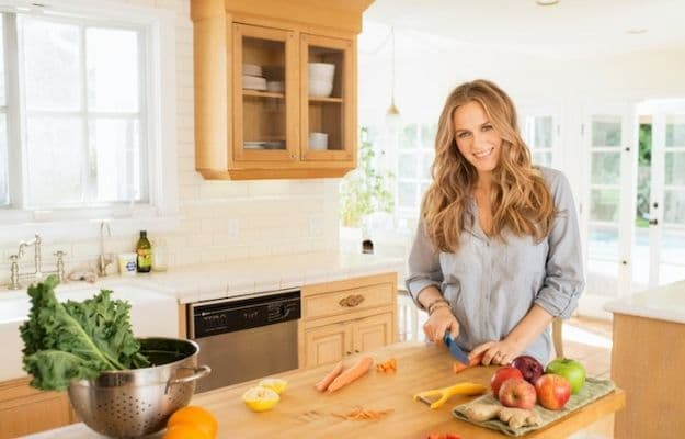Alicia Silverstone cutting a carrot and smiling-panda gossips | Alicia Silverstone | Famous Vegan Celebrities And Their Reasons For Living A Vegan Life
