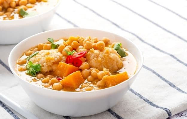 Curry with chickpeas, pumpkin, and cauliflower in white bowls on the table | Yellow Chickpea Cauliflower Curry | 9 Easy Frozen Vegan Meals To Make Ahead
