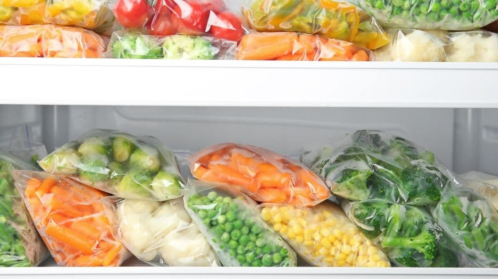 Plastic bags with deep frozen vegetables in refrigerator | feature | 9 Easy Frozen Vegan Meals To Make Ahead