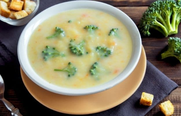 Vegetable and cheese cream soup with broccoli and croutons over wooden background | Vegan Broccoli Cheese Soup | 9 Easy Frozen Vegan Meals To Make Ahead