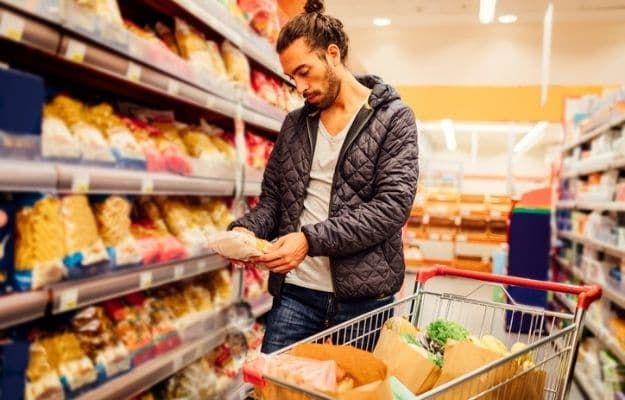a guy check food information at the supermarket | Preparation Is The Key | 6 Tips for New Vegans