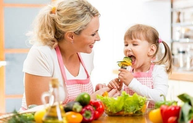 mom smiling and looking at her kid eating vegetable | Feature | What Parents Should Know About Vegan Health