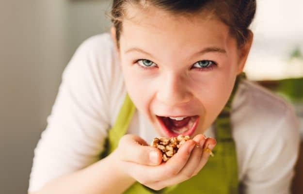 young girl eating nuts | Protein and Calories for Children on a Vegan Diet | What Parents Should Know About Vegan Health