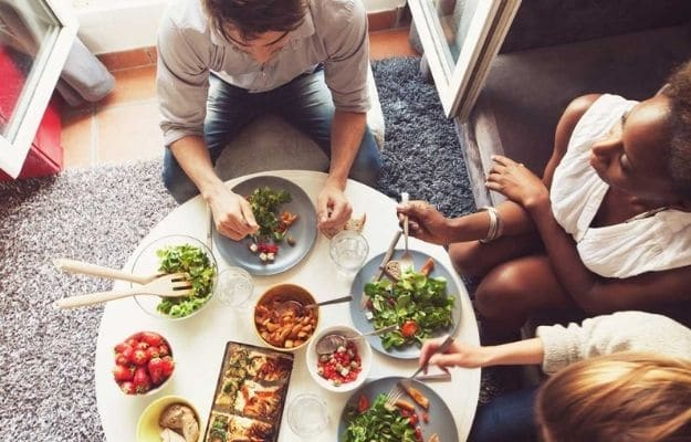 Friends laughing around a good meal | Vegetarian and Vegan Explained: A Clear Distinction