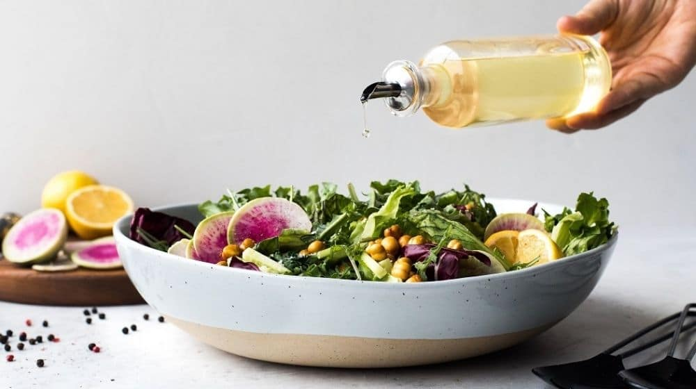a bowl of salad combining with a vegetable oil jug | Feature | The Healthiest 7 Vegan Cooking Oils