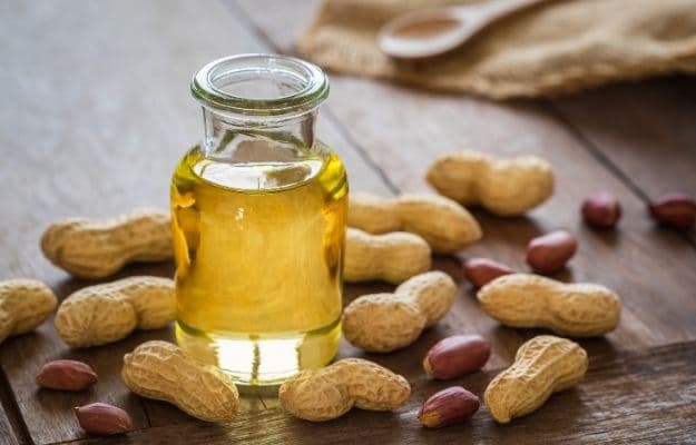 an oil jug is covered by peanuts | Peanut Oil | The Healthiest 7 Vegan Cooking Oils
