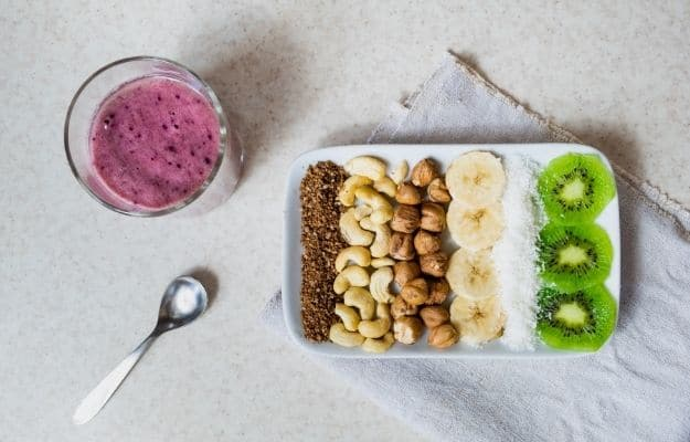 fruits and nuts cut into slices on plate with cup of juice and spoon a side | Deficiencies of Raw Food Diet And How To Address Them