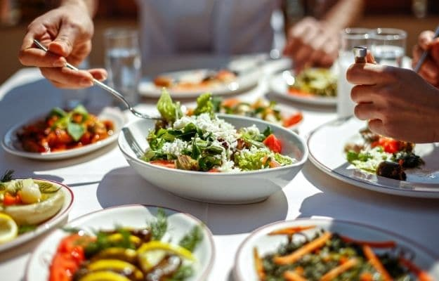 table full of vegetables and friends eating tasty lunch | Cleaner Food Source | 8 Reasons To Go Vegan