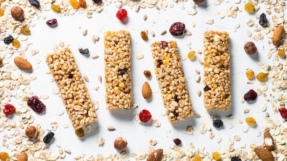 Cereal granola bar with nuts, fruit and berries on a white stone table-feature-ss | 9 Best Vegan Snacks You Won't Feel Guilty About Eating | feature