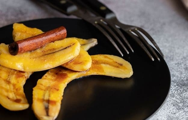 Fried bananas with cinnamon on the black plate-ca   9 Best Vegan Snacks You Won't Feel Guilty About Eating   Pan Fried Cinnamon Bananas