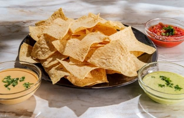 Tortilla chips tomato and guacamole salsa with Mexican cheese dip-ca | 9 Best Vegan Snacks You Won't Feel Guilty About Eating | Vegan Salsa and Homemade Tortilla Chips