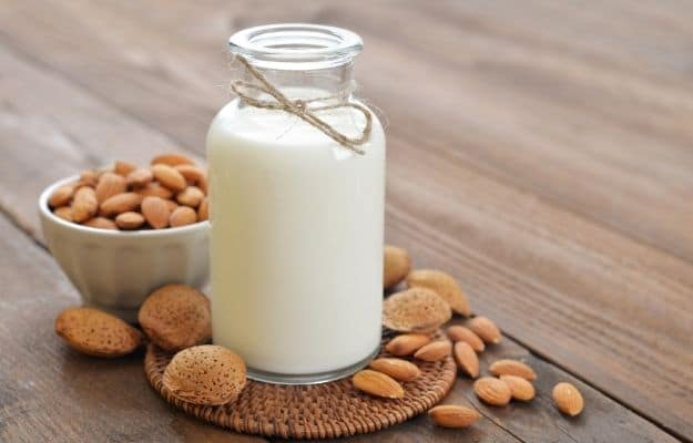 Almond white milk in a jug surounding with raw almond-ca | 8 Kinds of Vegan Milks and Their Benefits - No Reason For Dairy | Almond Milk