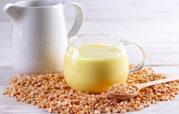 Pea yellow milk in a crystal cup next to white jug surounding with raw pea nuts-ca | 8 Kinds of Vegan Milks and Their Benefits - No Reason For Dairy | Pea milk