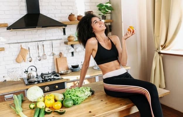 oung positive biracial woman in the kitchen with vegetables on the table-ss | Benefits Of A Keto Vegan Diet And What To Be Aware Of | Benefits of a Keto Vegan Diet